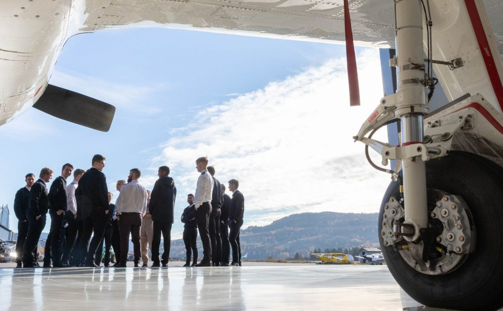 Students standing in cirkel outside the hangar of Flying Aces at Notodden airport, details of an airplane frames the picture